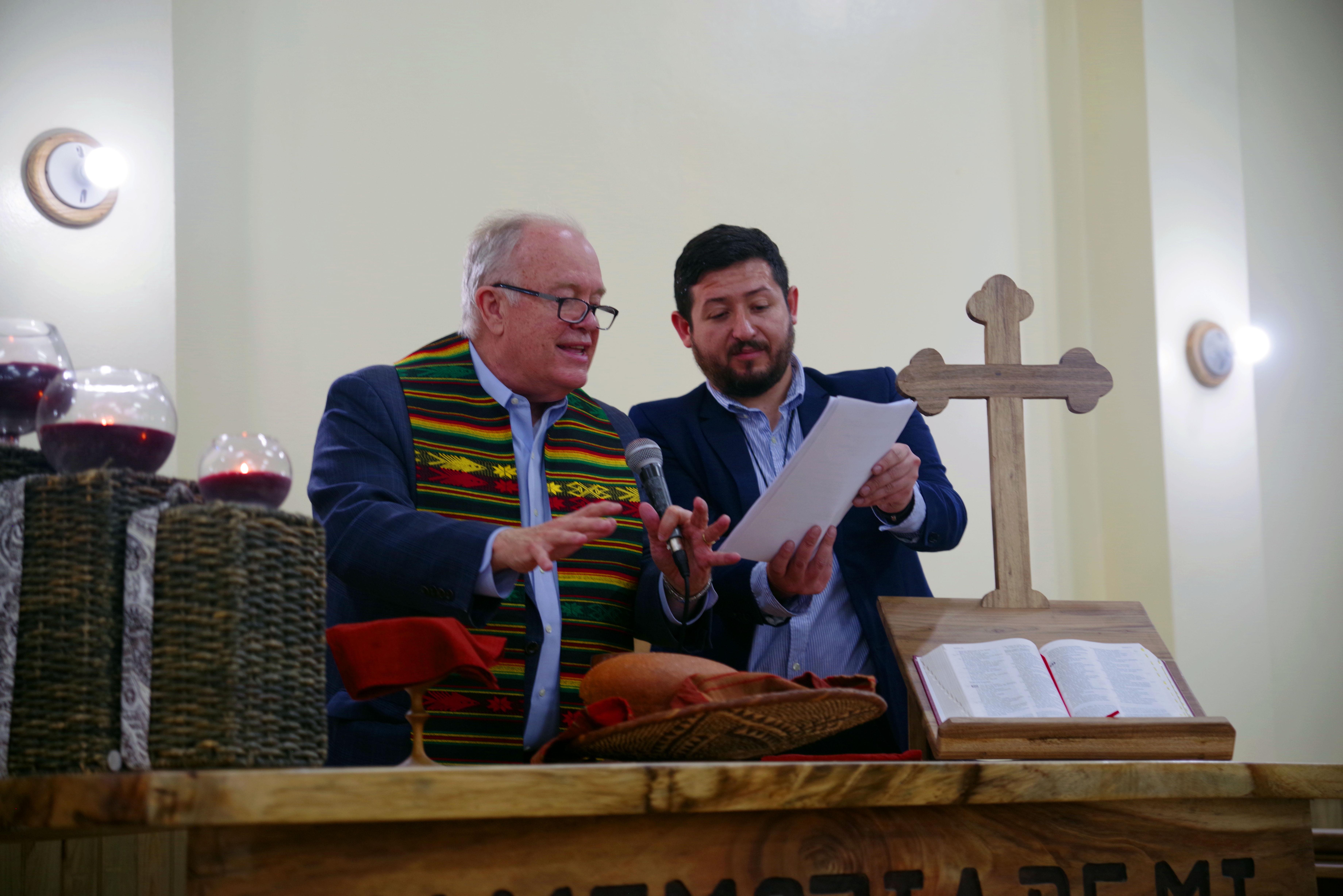 El Obispo Mikel McKee, consagra los elementos de la comunión asistido por el misionero Cristian Schlick. Foto Rev. Gustavo Vasquez, Noticias MU.