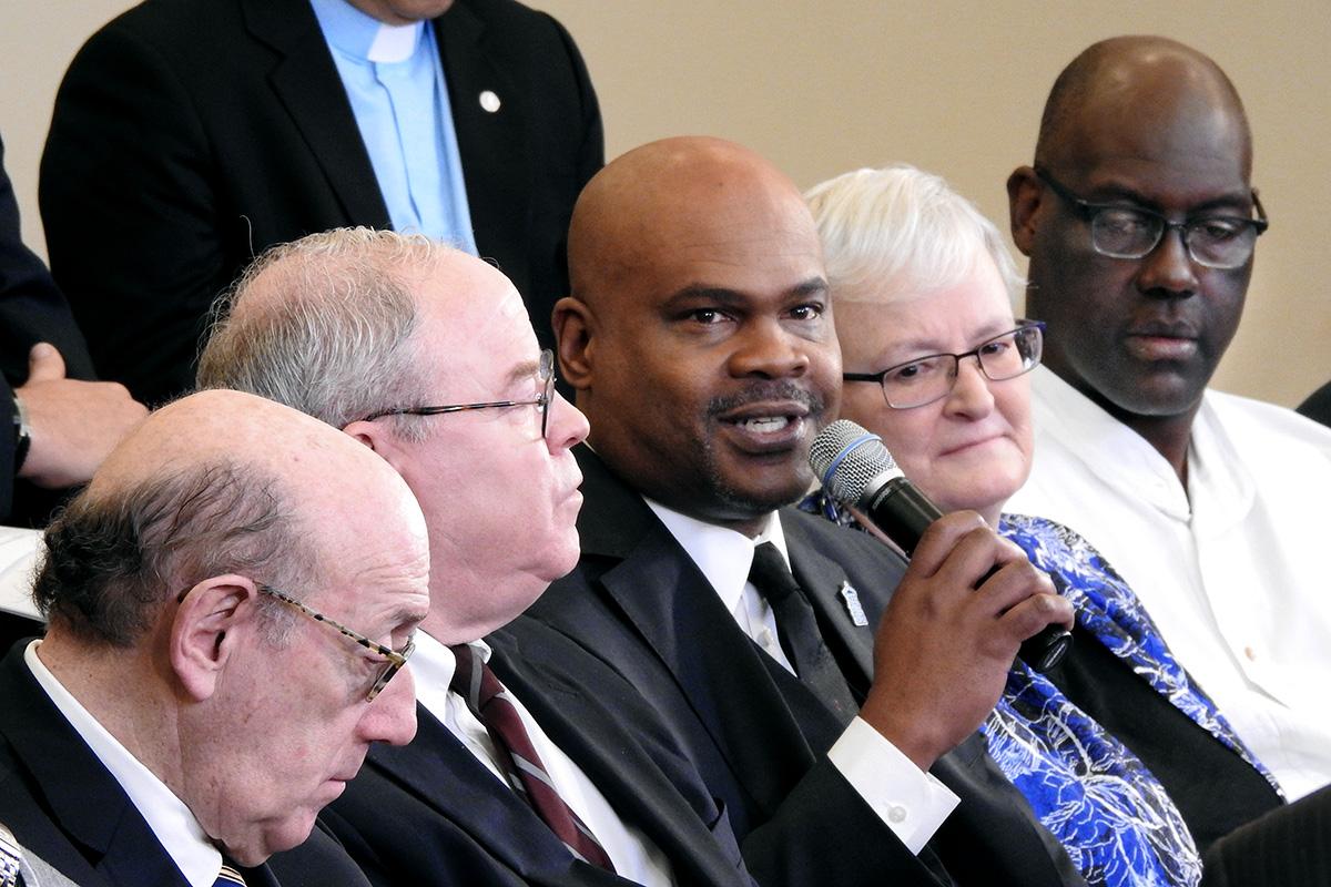 """El Rev. Junius Dotson (con micrófono), habla durante un panel de discusión en vivo en Tampa, Florida, con miembros del equipo que desarrolló el """"Protocolo de Reconciliación y Gracia a través de la Separación"""". Se reservan $ 39 millones en el plan para las iglesias de minorías étnico-raciales. """"La idea era ... dejar en claro que la iglesia tiene un compromiso con estas comunidades de color"""", dijo Dotson. Foto de Sam Hodges, Noticias MU."""