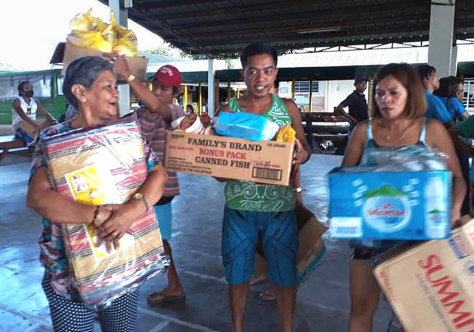 Evacuees in Mataas Na Kahoy in the province of Batangas, Philippines, receive relief goods from the Philippines Central Conference's Asuncion Perez Memorial Center. United Methodists are among the many people responding to the thousands displaced by the Taal volcano eruption Jan. 12 on Luzon Island. Photo courtesy of Liza A. Cortez.