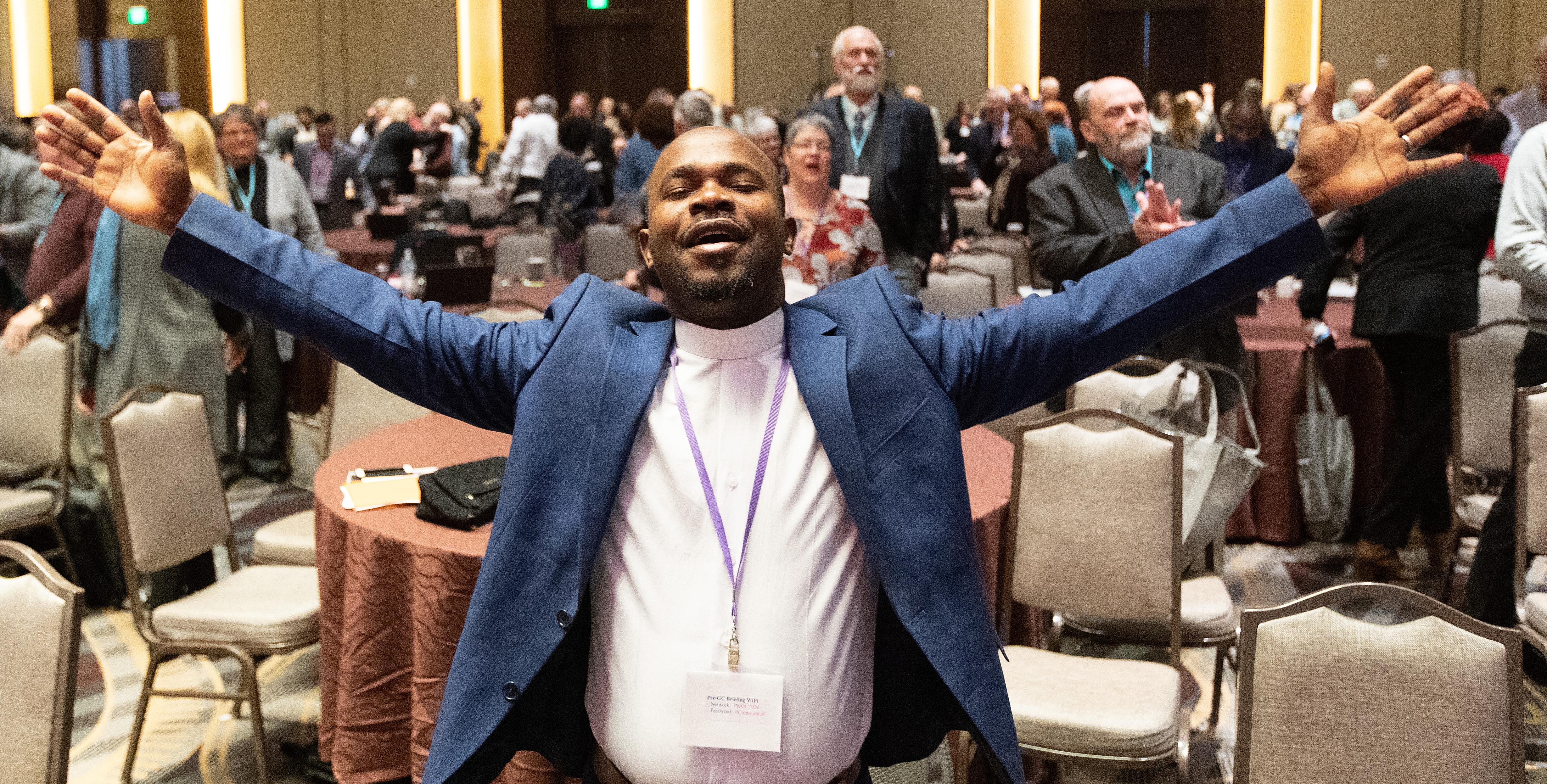 El Rev. Ande Emmanuel levanta los brazos en alabanza durante el culto de apertura en la reunión informativa de la Pre Conferencia General 2020 en Nashville, Tennessee. Foto de Mike DuBose, Noticias MU.