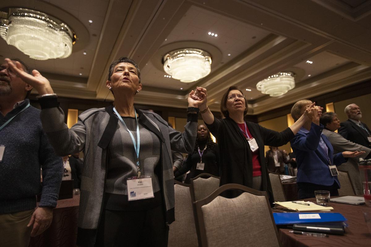 Kim Simpson, presidente da Comissão da Conferência Geral e Janice Griffith, Illinois Great Rivers, dão as mãos em oração durante o culto de abertura na Conferência Pré-Geral Metodista Unida de 2020, realizada em Nashville, Tennessee. Foto de Kathleen Barry, Notícias MU.