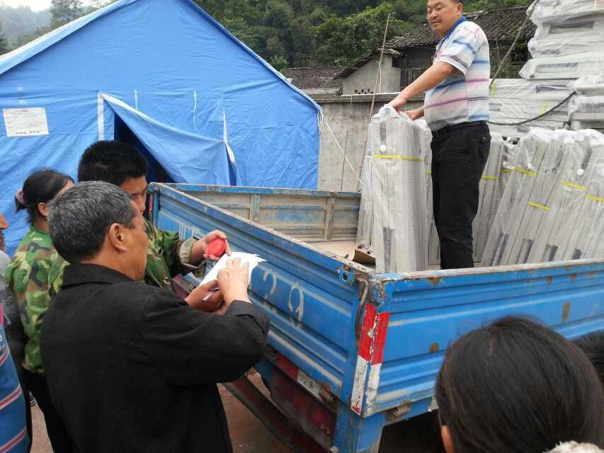 Amity Foundation staff members distribute folding beds to survivors following an April 20 earthquake in western China. Photo courtesy of the Amity Foundation.