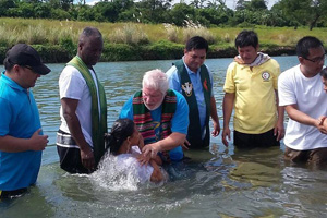 The Rev. Joey Galinato of Good Samaritan United Methodist Church, the Rev. Michael McQueen of St. James United Methodist Church and the Rev. Ronny Branen of Prospect United Methodist Church, all from the North Georgia Conference, join in baptizing 47 people in a river in Angat, Philippines. Photo by the Rev. Joey Galinato.