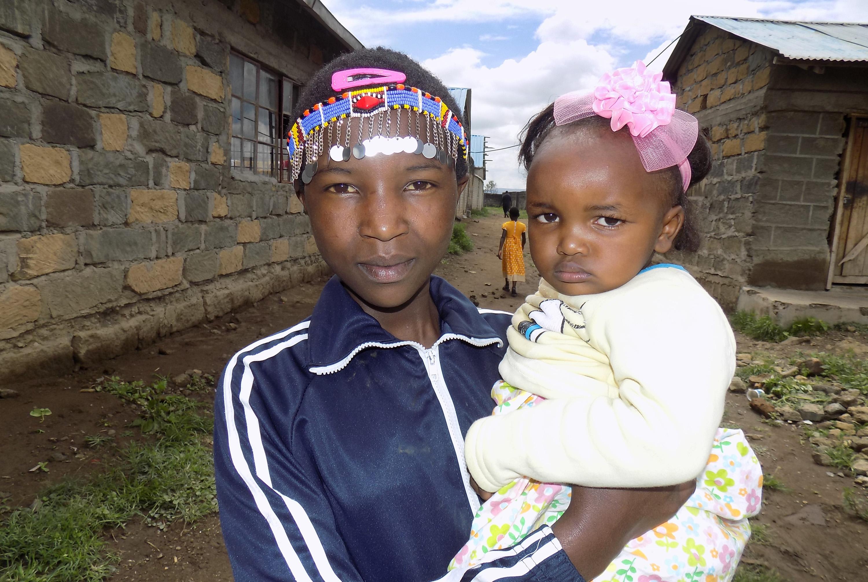Jecinta Nairesea, de 12 años, sostiene a su hija de 2 años Dorcus Nchorira, frente a la Iglesia Metodista Unida (IMU) La Trinidad en Gilgil, Kenia. La joven madre estaba entre quienes asistieron al campamento juvenil de la iglesia en diciembre. Jecinta, quien se vio obligada a casarse a los 9 años ahora asiste a Escuela Secundaria para Niñas Misión La Trinidad (Trinity Mission Girls High School). Foto de Faith Wanjiru, Noticias MU.