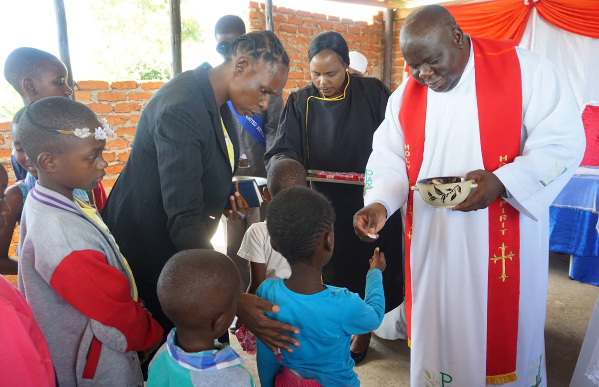 The Rev. Oscar Nyasha Mukahanana, Harare East District superintendent, distributes Holy Communion to children and others at Maximum Salvation United Methodist Church in Manresa, Zimbabwe. The church, near Chikurubi Maximum Security Prison, serves inmates, officers and their families. Photo by Kudzai Chingwe, UM News.
