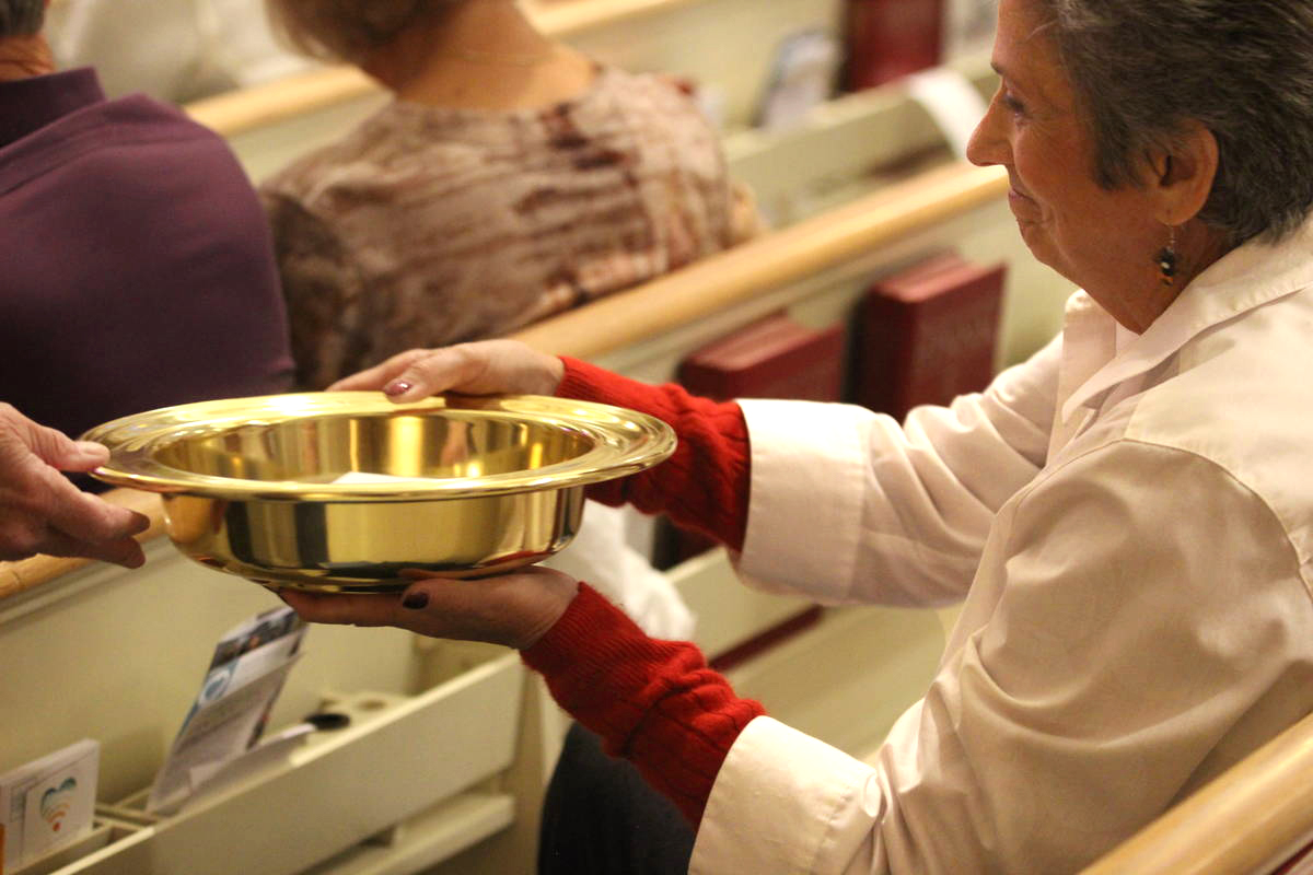 A woman holds an offering plate during a service at Boise United Methodist Church in Boise, Idaho. United Methodist collection rates in 2019 dipped below recent years, but the drop wasn't as steep as initially projected. Photo courtesy of the Marketing Department, United Methodist Communications.