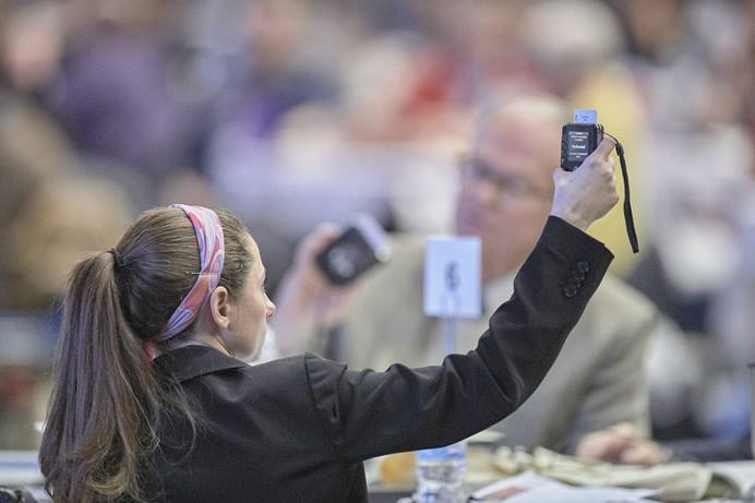A delegate holds her voting device aloft as she contemplates a Feb. 26, 2019, vote during the special General Conference in St. Louis. General Conference organizers have named a think tank to consider how best to process legislation at the 2020 General Conference. Photo by Paul Jeffrey, UM News.