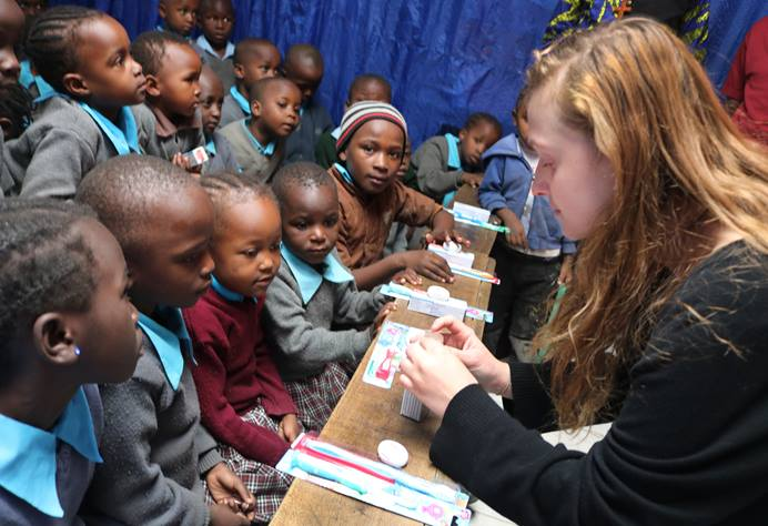 Grace Wall from Clarksbury United Methodist Church in Harmony, N.C., teaches students at New Hope Education Center how to brush and floss their teeth effectively. The primary school, run by Huruma United Methodist Church, supports orphans and other vulnerable children in the Mathare Valley slums on the eastern side of Nairobi, Kenya. Photo by Gad Maiga, UM News.