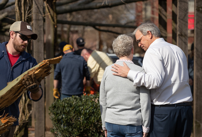 Bishop William McAlilly (right) comforts the Rev. Judi Hoffman in the park outside East End United Methodist Church in Nashville, Tenn., while volunteers clean up debris from a March 3 tornado that heavily damaged the church's sanctuary and offices. Photo by Mike DuBose, UM News.