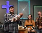 The Rev. Jason Martens (left) holds a baby during a baptism at Celebration United Methodist Church in Brandon, South Dakota. This is Martens' second restart. During his tenure at Unite Church in Salem, South Dakota, attendance increased from 25 to 115. Photo courtesy of Celebration United Methodist Church, Brandon, South Dakota Facebook page.
