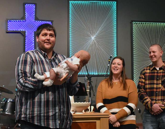 El Rev. Jason Martens (izquierda) sostiene a un bebé durante un bautismo en la IMU Celebration (La Celebración) en Brandon, Dakota del Sur. Este es el segundo proceso de renacimiento de iglesias que lidera Martens. Durante su permanencia en la IMU en Salem, Dakota del Sur, la asistencia aumentó de 25 a 115. Foto cortesía de la página de Facebook de la IMU Celebration.