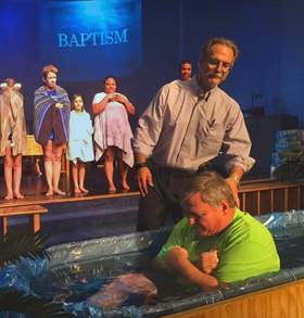 A man is baptized at Aloma United Methodist Church in Winter Park, Fla. The parish has closed its church building and is holding Sunday services in a local bar. Video image courtesy of Aloma United Methodist Church.