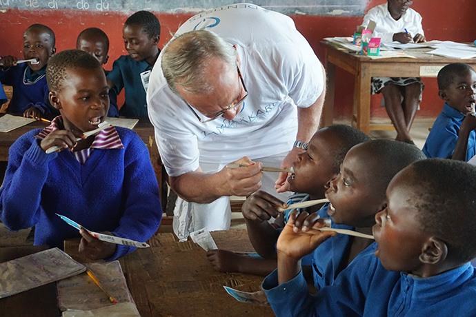 Dr. Kjell Gustafsson, a dentist from Sweden, helps children clean their teeth at Mutambara Central Primary School in Chimanimani, Zimbabwe. A Swedish dentists and hygienists visits rural Zimbabwe twice a year to provided free services to children, including oral health education, screenings, fillings and extractions of broken and decayed teeth. Photo by Kudzai Chingwe, UM News.