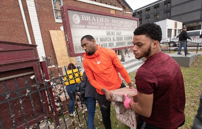 Gerald McRath (left) and Christian Hooper join with other volunteers to clear tornado debris outside Braden Memorial United Methodist Church in Nashville, Tenn. Both are members of the church. McRath played for the Tennessee Titans NFL team from 2009-2012. Photo by Mike DuBose, UM News.