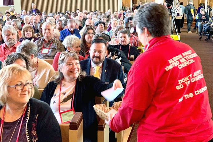 The Rev. Leslee Fritz (right), pastor of Albion First United Methodist Church, collects ballots during the vote by members of the Special Session of The Michigan Conference in Goodrich Chapel on March 7. Photo by Mark Doyal, courtesy of the Michigan Conference.