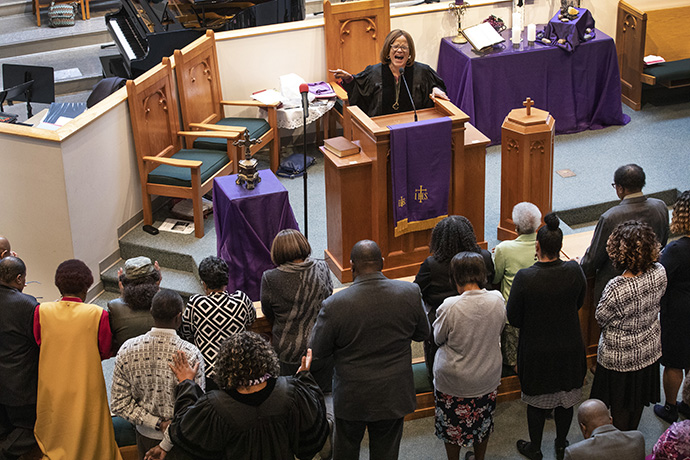 The Rev. Sheila Peters from Braden Memorial United Methodist Church preaches at the first Sunday service held at Gordon Memorial United Methodist Church following the March 3 tornado which heavily damaged Braden. Praying over attendees on the floor is the Rev. Paula B. Smith, pastor at Gordon Memorial. Photo by Kathleen Barry, UM News.