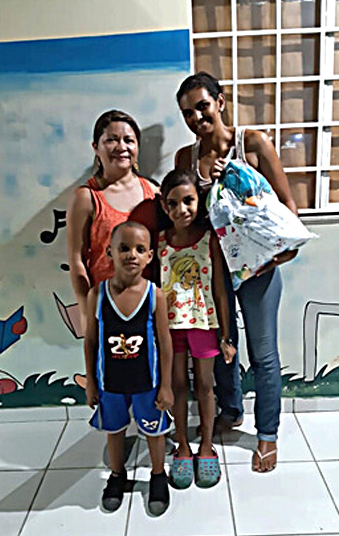 Familia de Charlys Morffi, reasentada en Betim, estado de Minas Gerais. Marjorys Venezuela León Escobar, a la derecha, es la esposa de Morffi. Zarick Cristina Morffi (8), es su hija y Jeremias Daniel Morffi (6), su hijo. La directora del programa Boa Vista, Marcia Cardias (esquina izquierda). Esta familia se vio afectada y su vida se transformó con la entrega del kit de emergencia. Foto cortesía de Iglesia Metodista en Brasil