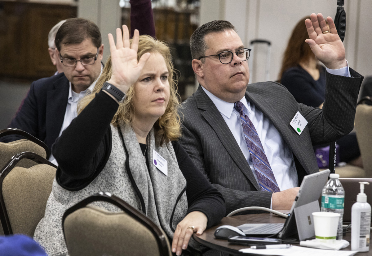 Christine Dodson and the Rev. David Bell, General Council of Finance and Administration board members, raise their hands during a meeting at Scarritt Bennett Center in Nashville, Tenn. The board voted to send the smallest budget the General Conference in more than 30 years. Photo by Kathleen Barry, UM News.