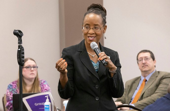 The Rev. Kennetha J. Bigham-Tsai speaks during the meeting of the General Council of Finance and Administration board. Listening in the background are Sara Hotchkiss and the Rev. Gary Graves. Photo by Kathleen Barry, UM News.