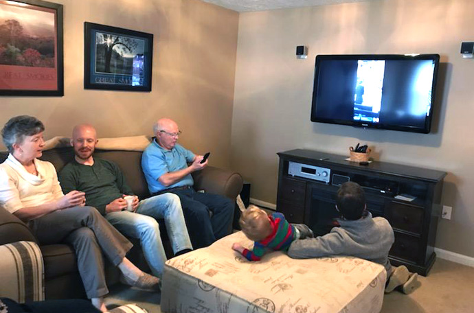 Members of the Williams family gather at the home of David (right on couch in blue shirt) and Susan Williams (left on couch in white shirt), to watch a livestream of the 11:15 a.m. service of Christ Church United Methodist Church in Louisville, Ky. Seated on the floor to far right is their son, Ben Williams, a musician at the church. Photo by Lesley Williams, courtesy of the Kentucky Conference.