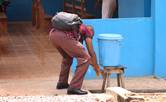 A visitor to United Methodist Mercy Hospital in Bo, Sierra Leone, washes his hands at a wash station before entering the hospital on March 16. Amid coronavirus concerns, the use of handwashing stations, previously used during the country's fight against Ebola, has been stepped up in public places, including hospitals, banks and schools. Photo by Phileas Jusu, UM News.