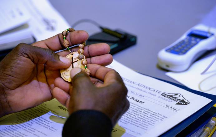 A delegate handles prayer beads during prayer at the 2016 United Methodist General Conference in Portland, Ore. With the coronavirus delaying the 2020 General Conference, church leaders hope United Methodists can experience more time to pray and be the church. File photo by Paul Jeffrey, UM News.