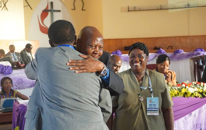 The Rev. Josephat Banda congratulates his new district superintendent of diaspora, The Rev. Stephen Mukata (center), as Mukata's wife, Perpetua Mukata, looks on at Old Mutare Mission in Mutare, Zimbabwe, during his appointment in 2018. Mukata oversees diaspora in the United Kingdom, Australia, New Zealand and Canada. Photo by Kudzai Chingwe, UM News.