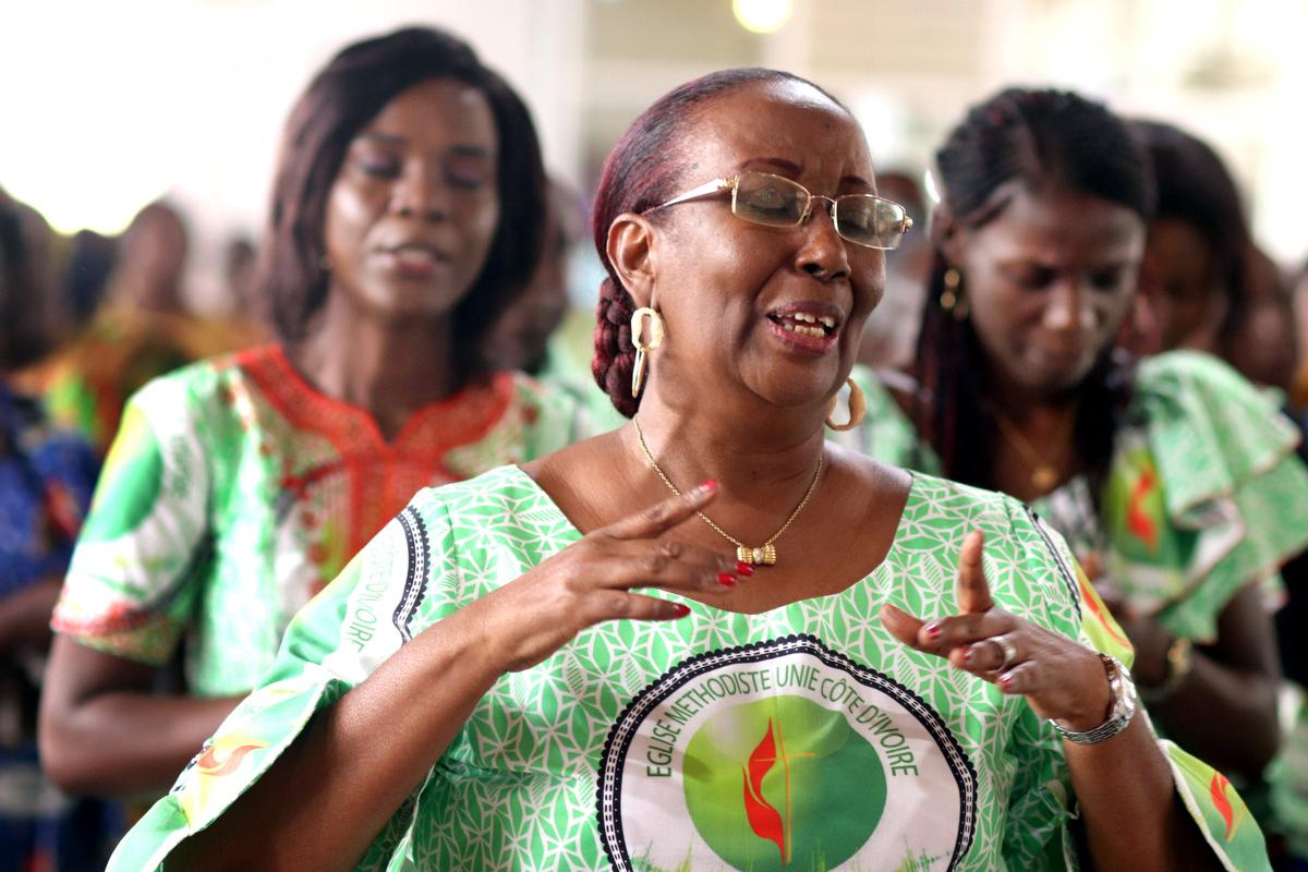 Lydie Acquah (à l'avant) se joint aux chants lors de la célébration du 10ème  anniversaire de La Voix de l'Espérance, la station de radio de l'Église Méthodiste Unie de Côte d'Ivoire, à l'église Méthodiste Unie Jubilé d'Abidjan Cocody. Acquah est la directrice de la station. Photo de Isaac Broune, UM News.