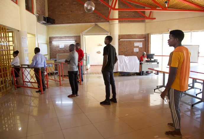 Students and staff practice social distancing in order to reduce the risk of spreading the coronavirus as they wait to enter the dining hall at Africa University in Mutare, Zimbabwe. The cafeteria has changed serving and seating arrangements, and meal times have been extended to three hours so those on campus do not all have to be served at the same time. Photo by the Africa University office of Advancement and Public Affairs.