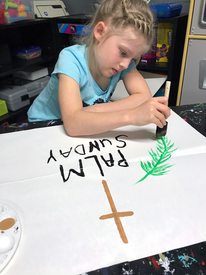 Zoey Rosenbaum, 8, works at home on a Palm Sunday banner. Her church, Trinity United Methodist in Clearfield, Pa., is worshipping online because of the coronavirus threat but hopes to have members drive around town on Palm Sunday afternoon, displaying signs that proclaim the day. Photo courtesy of Trinity United Methodist.