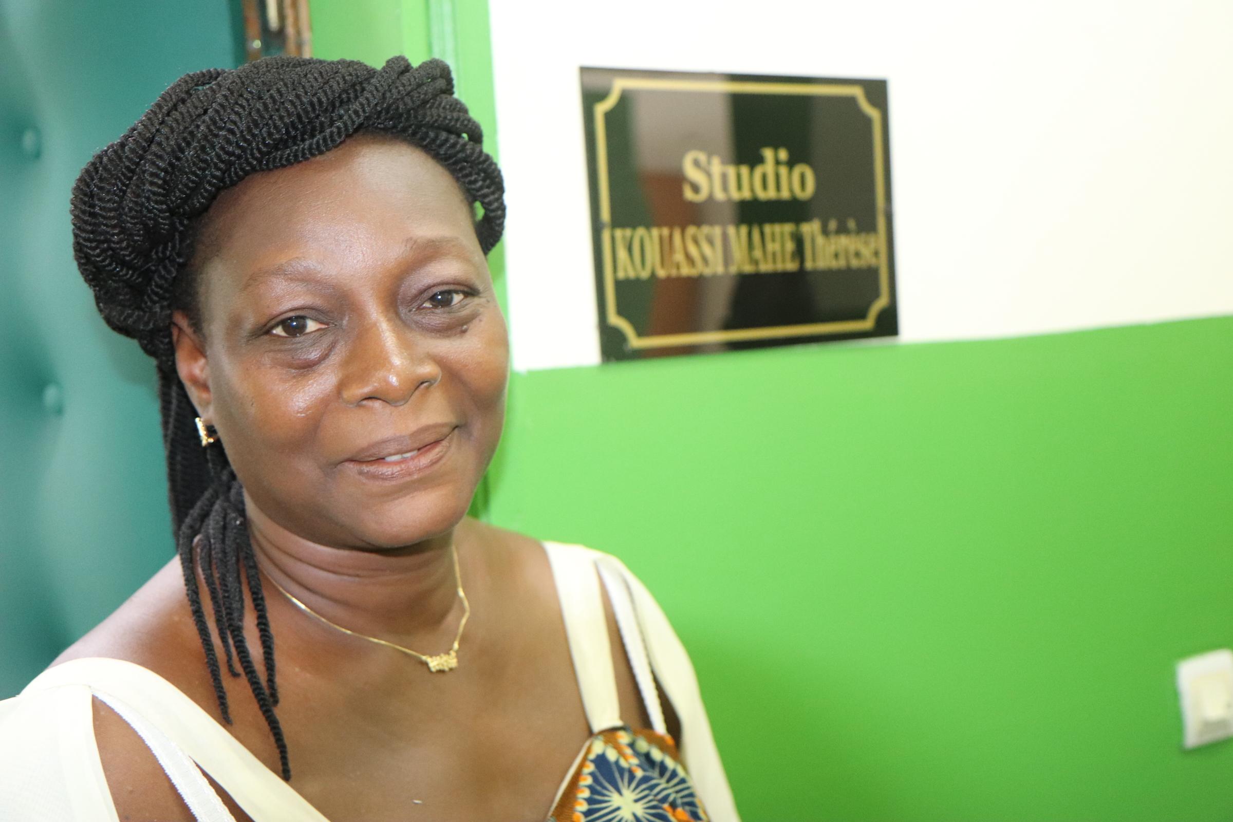 Mme Marcelle Ekou se tient devant le studio de diffusion qui porte désormais le nom de sa mère Kouassi Mahé Thérèse honorée pendant la semaine des festivités marquant les 10 années d'existence de La Voix de l'Espérance. Thérèse fait partie des bénévoles qui animent les émissions en langues vernaculaires. Photo de Isaac Broune, UM News.