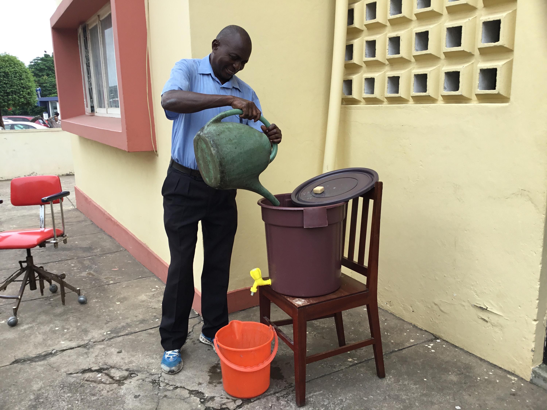 Senhor Alfredo Rafael Chume, um dos funcionários da Igreja que guarnece os Escritórios, adiciona água com produtos químicos a entradas dos Escritórios Centrais. Foto de João Filimone Sambo.