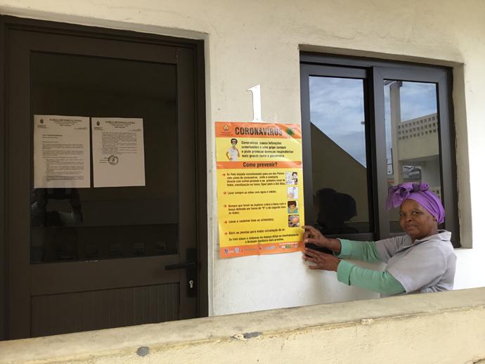 Rita Samuel aponta para o cartaz e o comunicado episcopal que falam das medidas a serem tomadas face ao COVID-19. Foto de João Filimone Sambo.