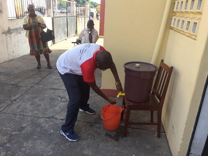 Reverendo Vicente Mauaie lavando as suas mãos antes de entrar no edifício da IMUM em Maputo. Foto de João Filimone Sambo