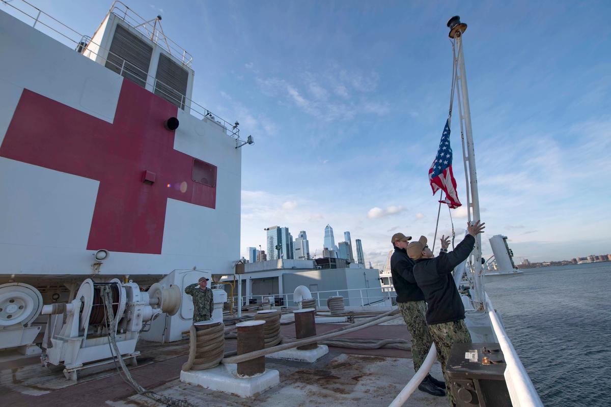 """Los marineros en el buque hospital USNS Comfort elevan los colores mientras el barco está amarrado en el puerto de Nueva York en apoyo de los esfuerzos de respuesta COVID-19 de la nación. Los líderes metodistas unidos están pintando una imagen aleccionadora del impacto del coronavirus en Nueva York y Nueva Jersey. """"Este es nuestro nuevo 11 de septiembre en Nueva York"""", dijo el obispo del área de Nueva York Thomas J. Bickerton. Foto cortesía de Sara Eshleman, Marina de los EE. UU."""