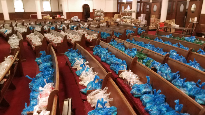 Food parcels line the pews at the United Methodist Church of St. Paul & St. Andrew in New York. The West Side Campaign Against Hunger — a supermarket-style food pantry program founded and actively supported by St. Paul & St. Andrew — has moved its operations there from the basement's fellowship hall. Starting the week of April 6, the ministry will begin bagging food for Bellevue Hospital in Manhattan. Photo by the Rev. K Karpen.