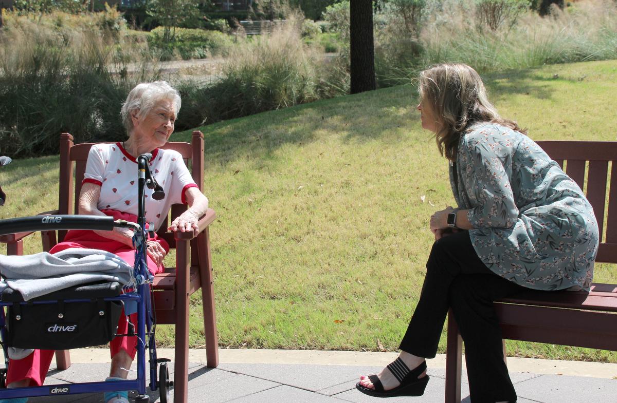 A Revda. Kellie Sanford (à direita) pratica o distanciamento social enquanto visita um morador da comunidade CC Young Senior Living, em Dallas. Sanford, um pastor local licenciado na Igreja Metodista Unida, serve como capelão da instalação. Foto de Jennifer Griffin.