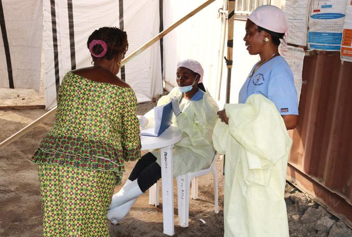 L'infirmière Anny Butunga (assise) prend des informations sur un patient dans une chambre d'isolement d'Ebola à l'hôpital Méthodiste Uni Irambo à Bukavu, RD Congo, sous le regard d'une autre infirmière. Toutes les chambres d'isolement d'Ebola des hôpitaux Méthodistes Unis de la région sont en train d'être transformées en centres d'isolement du COVID-19. Photo de Philippe Kituka Lolonga, UM News.