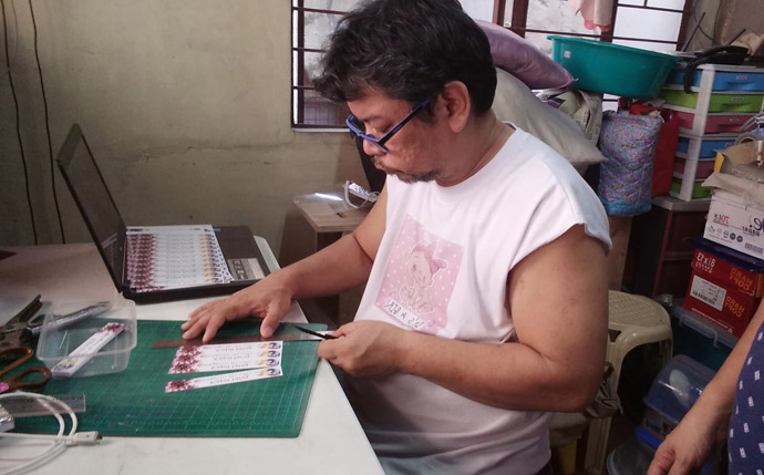 Melvin Nor S. Ramos, a layperson from Kawan ni Kristo United Methodist Church in the South Bulacan District of the Philippines, works on labels for his DIY face shields. Together with his family and other church members, he pooled resources to create the needed protection for local hospitals and health centers in the fight against the coronavirus. Photo courtesy of Melvin Nor S. Ramos.