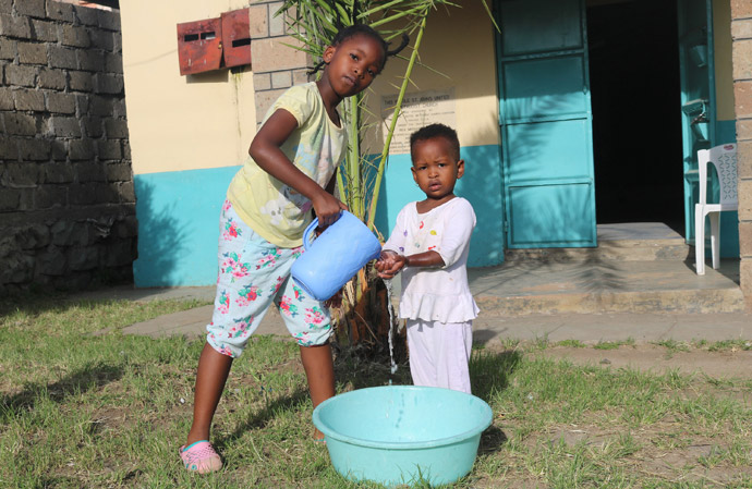 Nine-year-old Shantel Resse washes the hands of her younger sister, Reina Muthoni, at Kayole St. John's United Methodist Church in Nairobi, Kenya. Churches in Kenya are urging members to wash their hands using soap or hand sanitizer to stop the spread of the coronavirus. Photo by Gad Maiga, UM News.