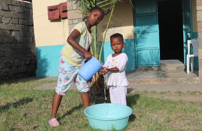 Shantel Resse, neuf ans, lave les mains de sa petite sœur, Reina Muthoni, à l'église Méthodiste Unie Kayole St. John's de Nairobi, au Kenya. Les églises du Kenya exhortent leurs membres à se laver les mains avec du savon ou du désinfectant pour mains afin d'arrêter la propagation du coronavirus. Photo de Gad Maiga, UM News.