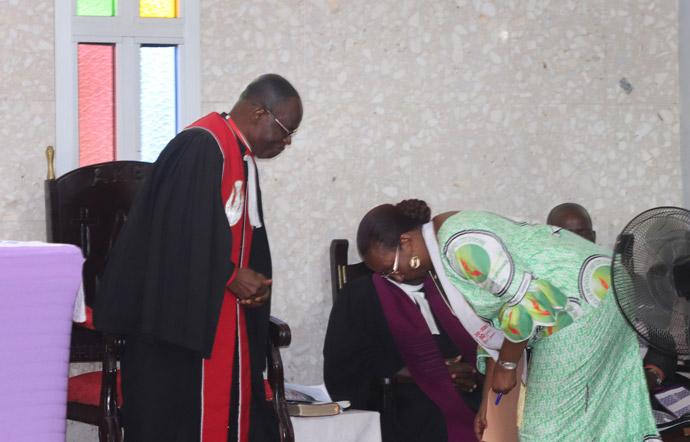 L'évêque de Côte d'Ivoire Benjamin Boni et Lydie Acquah, directrice de la radio La Voix de l'Espérance, se saluent tout en évitant de se serrer la main lors du culte de clôture de la célébration des 10 ans de la radio, le 15 mars. L'Eglise insiste sur les mesures visant à freiner la propagation de COVID-19. Photo de Isaac Broune, UM News.