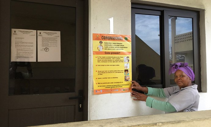 United Methodist Rita Samuel points to a poster that shares tips for stopping the spread of the coronavirus in Maputo, Mozambique. Photo by João Filimone Sambo, UM News.
