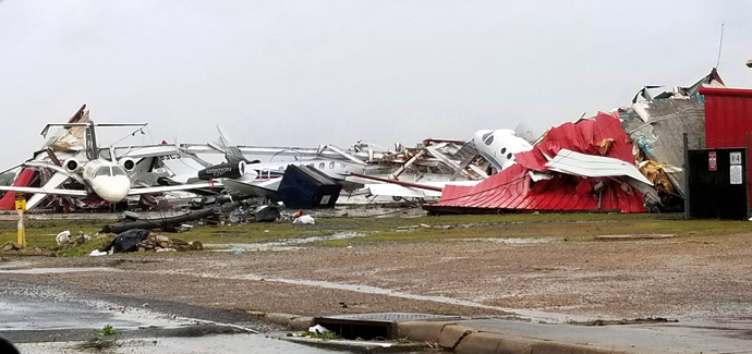 """View of the destroyed hangar and multiple damaged private planes at Monroe Regional Airport, Monroe, La., after devastating storms swept across the southern United States April 12. The image, shared from the City of Monroe's Twitter account, was accompanied by the notice: """"Due to weather conditions and debris removal from the runways …  all flights at the Monroe Regional Airport are cancelled until further notice."""" Photo courtesy of City of Monroe."""