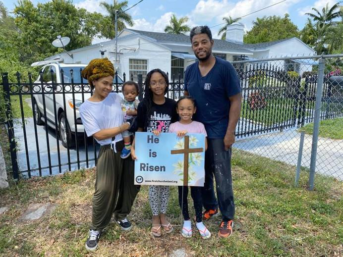 A family from First United Methodist Church of Miami stands with a yard sign given to them by the church. Photo by Kipp Nelson, First United Methodist Church of Miami.