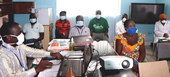 Dr. Daniel Ahui (left), a specialist in infectious and tropical diseases and director of Dabou United Methodist Hospital in Dabou, Côte d'Ivoire, trains pharmacy and laboratory staff on how to deal with suspected and confirmed COVID-19 cases. Although there are no cases of the coronavirus in this city yet, the hospital is taking steps to avoid being caught off guard. Photo by Isaac Broune, UM News.