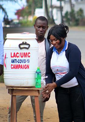 Lango W. Toe, directrice de santé de l'Église Méthodiste Unie du Libéria, fait une démonstration de lavage des mains dans l'une des stations installées dans les rues de Sinkor, au Libéria. Photo de E Julu Swen, UM News.