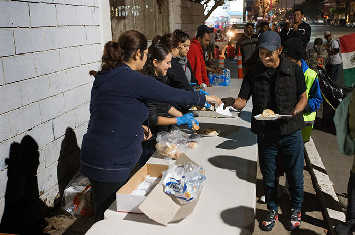 Volunteers from the Methodist Church of Mexico feed people outside a makeshift camp for migrants at the Benito Juarez sports complex in Tijuana, Mexico, in December 2018. The program was forced to close April 3 due to the coronavirus. File photo by Mike DuBose, UM News.
