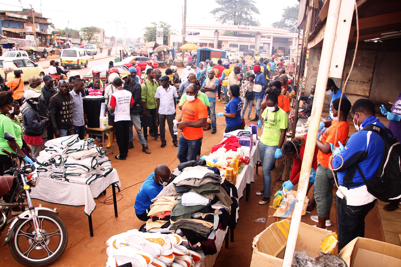 Ndobe Ebeneza Mosima, pasteur de l'église Méthodiste Unie Ebenezer de Yaoundé (en orange au centre) s'adresse à la population venue assister à la campagne de sensibilisation contre le COVID-19. Photo de Collette Ndpbe, UM News.
