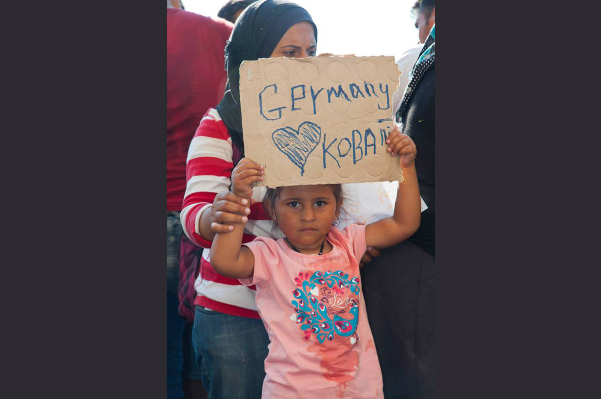 A young migrant girl hoping to reach Germany with her family holds up a sign inside the Hungarian border.  Photo by Oláh Gergely Máté.